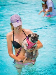 A pug is held in the water during the fourth annual