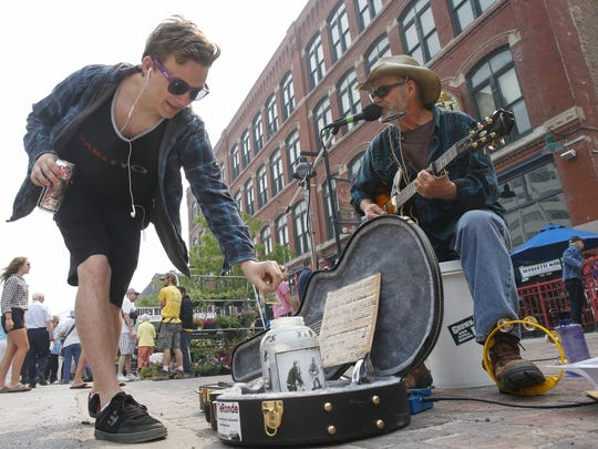 "Madrid musician Matt Teronde, known as ""Sweet Tater,"" receives a tip as he plays Saturday morning. Madrid musician Matt Teronde, known as ""Sweet Tater,"" receives a tip as he plays during the opening day of the 2016 downtown farmers market in Des Moines."
