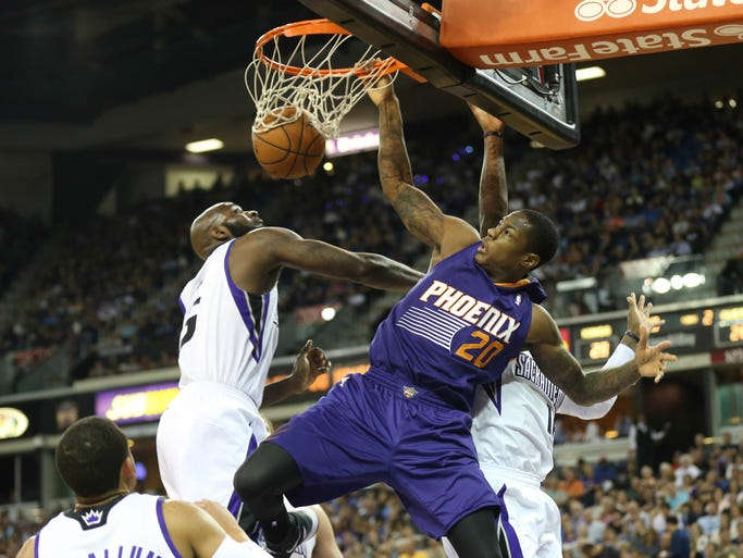 Phoenix Suns guard Archie Goodwin (20) dunks the ball between Sacramento Kings forward Quincy Acy (5) and Sacramento Kings guard Ben McLemore (16) during the second quarter at Sleep Train Arena on April 16, 2014.