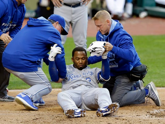 Kansas City Royals' Alcides Escobar is helped up by trainers after getting hit by a pitch from Cleveland Indians starting pitcher Danny Salazar in the fifth inning of a baseball game, Wednesday, April 29, 2015, in Cleveland. Escobar left the game. He walked to the dugout with help from the trainers and was taken to the clubhouse. (AP Photo/Tony Dejak)