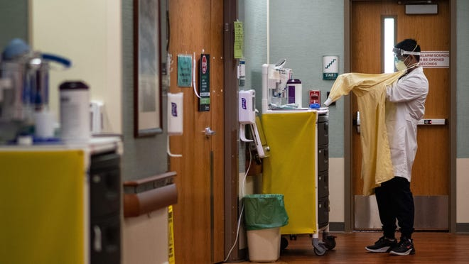 Akhil Sharma, a Michigan State University resident doctor, puts on a gown Oct. 20 before seeing a COVID-19 patient at Sparrow Hospital's intensive care unit in Lansing.