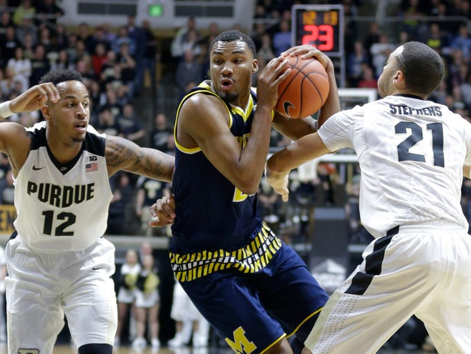 Michigan guard Zak Irvin (21) is fouled as he cuts