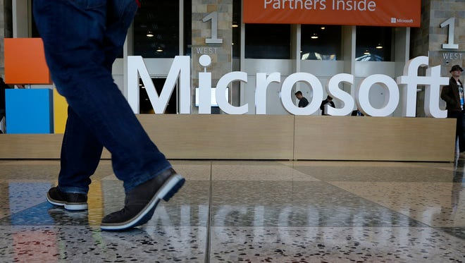 In this April 28, 2015 file photo, a man walks past a Microsoft sign set up for the Microsoft BUILD conference at Moscone Center in San Francisco. Starting next year, P Photo/Jeff Chiu, File) ORG XMIT: NYBZ101