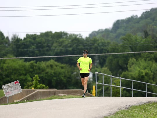 A jogger runs on the Lunken Airport bike path.