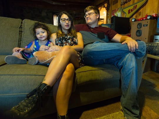 Zach Eason, 20, Luz Skywalker, 21, and their daughter Luna, 2, relax in the entertainment room of Zach's home on Tuesday.