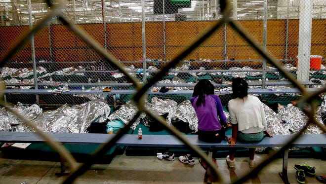 Two young girls watch a World Cup soccer match on a television from their holding area on June 18, 2014, in Nogales, Arizona. They are among hundreds of immigrant children being processed and held at the U.S. Customs and Border Protection Nogales Placement Center.