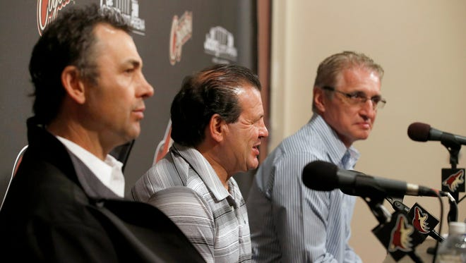 """Members of the gold medal 1980 """"Miracle on Ice"""" U.S. hockey team, Neal Broten, left, Mike Eruzione and Buzz Scheider, right, talk to the media prior to being honored at an NHL hockey game between the Chicago Blackhawks and the Phoenix Coyotes, Friday Feb. 7, 2014, in Glendale, Ariz."""