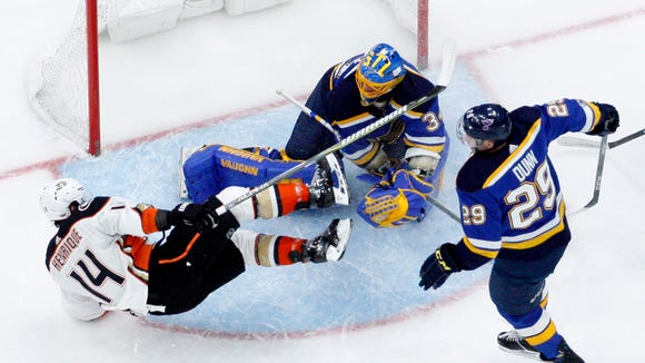 Anaheim Ducks' Adam Henrique (14) falls over St. Louis Blues goalie Jake Allen as Blues' Vince Dunn (29) watches during the first period of an NHL hockey game Thursday, Dec. 14, 2017, in St. Louis. (AP Photo/Jeff Roberson)