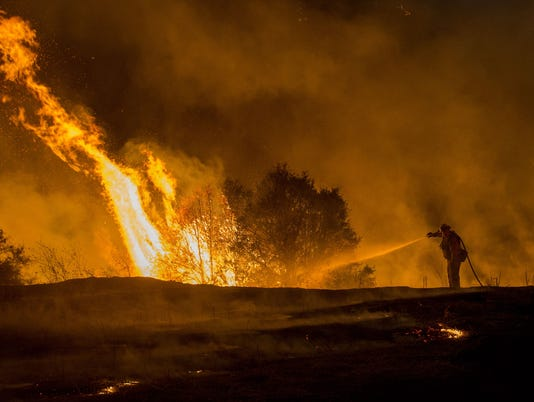 Thousands evacuated as wildfires race through California