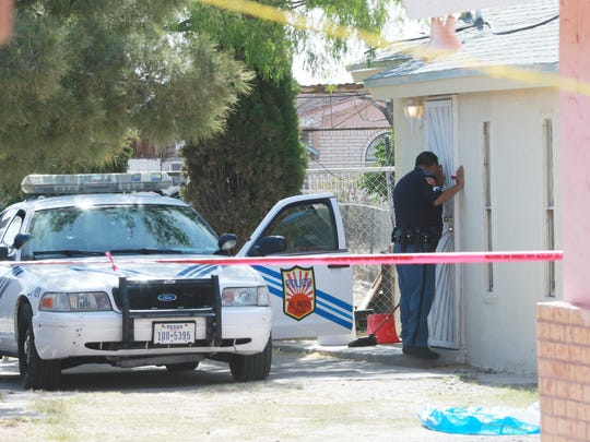 An El Paso police officer peers into a home on Apodaca Place in the Lower Valley.