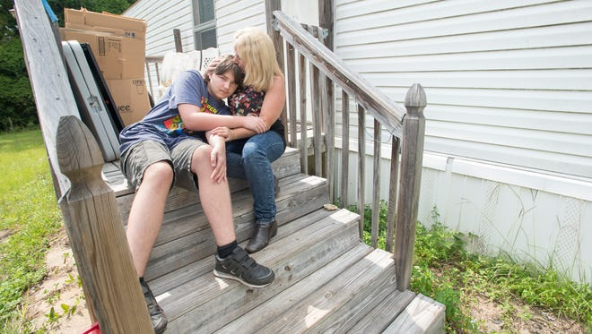 Melissa Nason and her son Ayden, 14, sit outside of their home in the Westgate Mobile Park in Milton on Wednesday, July 18, 2018.  Because the property owner hasn't fixed the broken septic system and water has subsequently been shut off to the mobile park since July 13th, residents are needing to find new places to live.