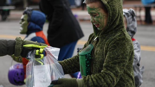 In this Oct. 31, 2019 file photo, 7-year-old Campbell May, of Grove City, receives a bag of candy from a local vendor while dressed up as a dinosaur at Boo Off Broadway & Trick-or-Treat in Grove City.