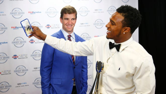 Lakewood football player Amir Tyler does some snapchatting backstage in front of NY Giants quarterback Eli Manning during the Jersey Shore Sports Awards dinner at Monmouth University Monday, June 13, 2016.   Tyler won the Courage Award.