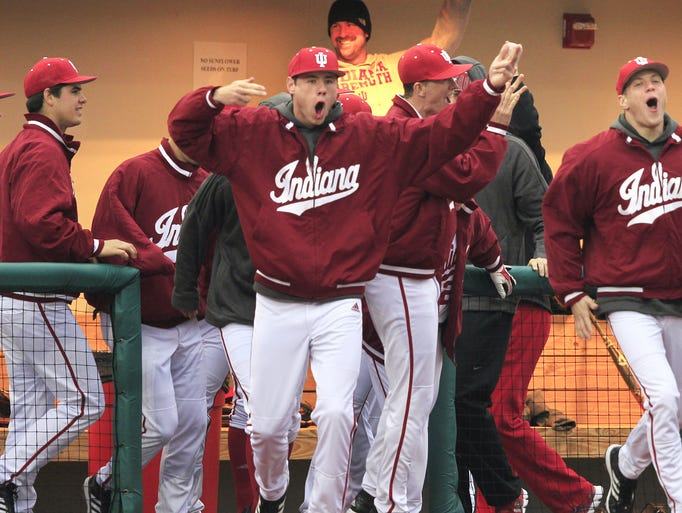 The Indiana University baseball team rushes out of the dugout onto the field to celebrate with teammates after the last out of the Hoosiers' 9-3 victory over Louisville at Bart Kaufman Field in Bloomington on Wednesday, March 19, 2014. The Hoosiers scored six runs in the fifth inning and came back from a 3-1 deficit for the win in windy and cold conditions.