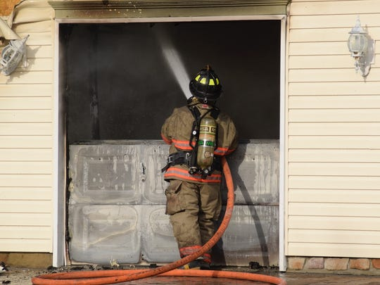 A firefighter with Southeastern Adams Volunteer Emergency services helps put out a house fire on Tuesday, March 1. The home, on the first block of Los Alamitos Circle in Conewago Township, had damage to the garage and smoke and heat damage on the first and second floors, police said.