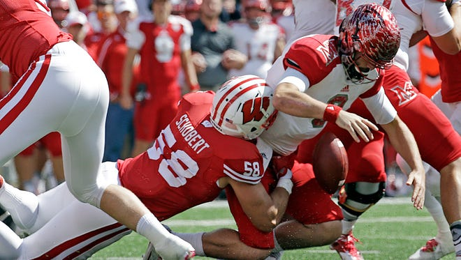 Miami quarterback Drew Kummer fumbles as he is sacked by Wisconsin's Joe Schobert.