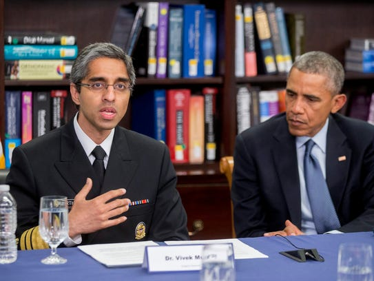 President Obama listens to Surgeon General Vivek Murthy