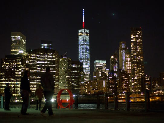 The One World Trade Center spire is lit blue, white
