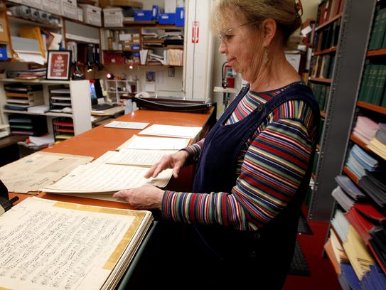 Mary Judge, principal librarian, looks at old sheet