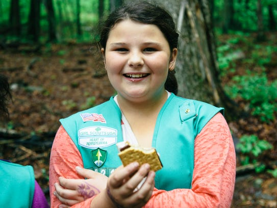 A Girl Scout enjoys a s'more.