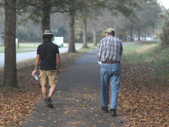 Paul Bailey, left, and Ben Hagler, right, walk a mile