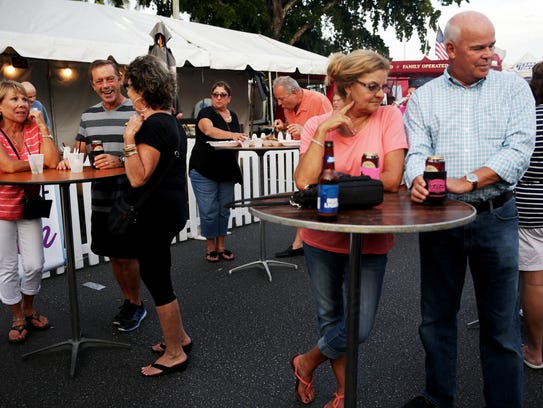 Attendees eat and drink during the Stone Crab Festival