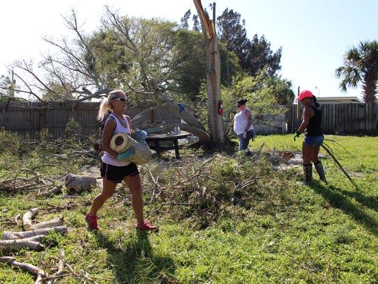 Denise Buchanan and volunteers clean up a fallen tree