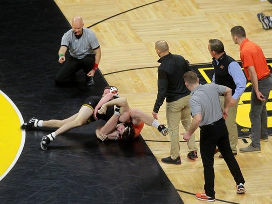 Oklahoma State coaches watch Keegan Moore wrestle Iowa's