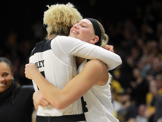 Iowa seniors Chase Coley, left, and Carly Mohns hug