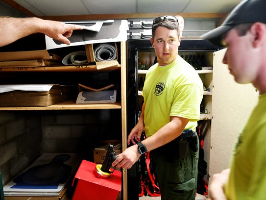 Hunter Hamm assists classmates with ensuring handguns are unloaded as they head to a drill at a firing range in Sylva as part of the National Park Service Seasonal Law Enforcement Training Academy April 12, 2018.