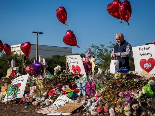 A man views a memorial for the 17 students killed in