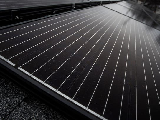 Newly-installed solar panels sit on the roof of First