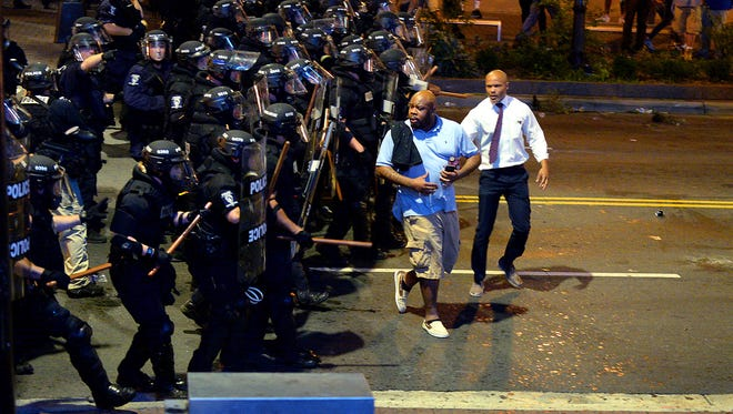 Charlotte-Mecklenburg police officers begin to push protesters from the intersection near the Epicentre in Charlotte, N.C. Wednesday, Sept. 21, 2016.  Authorities in Charlotte tried to quell public anger Wednesday after a police officer shot a black man, but a dusk prayer vigil turned into a second night of violence, with police firing tear gas at angry protesters and a man being critically wounded by gunfire.