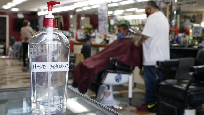 A bottle of hand sanitizer sits on a counter as Edgar Gomez has his hair cut by George Garcia, owner of George's Barber Shop, Tuesday, July 14, 2020, in San Pedro, Calif.