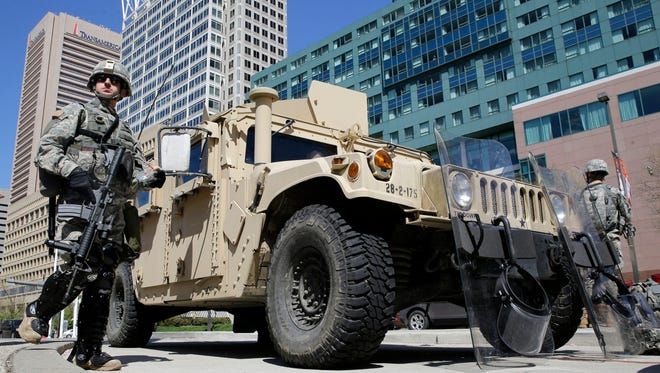 Maryland National Guardsmen patrol near downtown businesses in Baltimore on Tuesday, a day after looting and arson erupted following the funeral of Freddie Gray. Gray died from spinal injuries about a week after he was arrested and transported in a Baltimore Police Department van.