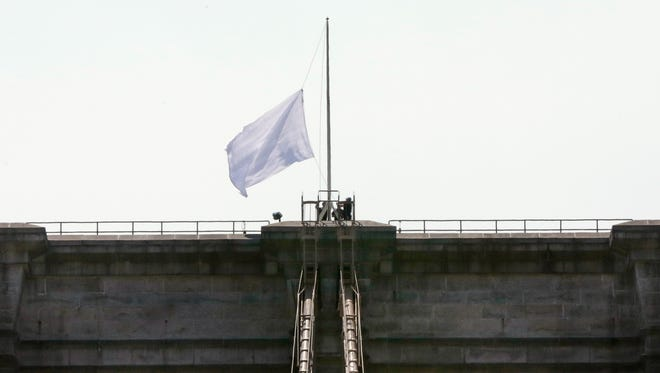 New York City Police officers lower a white flag flying atop the west tower of New York's Brooklyn Bridge, Tuesday, July 22, 2014. Two large American flags atop the Brooklyn Bridge were replaced sometime during the night with white banners. Police crime scene and intelligence detectives were investigating how the flags were switched out on the famed span that connects Brooklyn and Manhattan, and there were no reports of suspicious activity, police said.