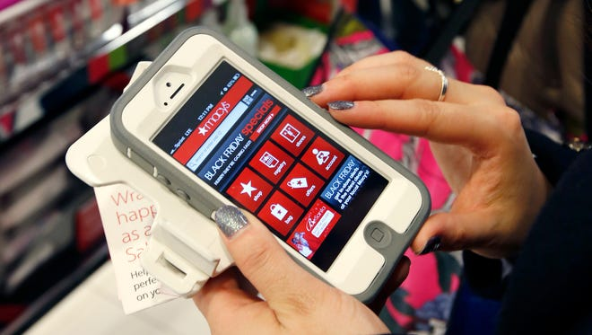 """FILE - In this Friday, Nov. 23, 2012, file photo, Tashalee Rodriguez, of Boston, uses a smartphone app while shopping at Macy's in downtown Boston. Shoppers are flocking online Monday, Nov. 28, 2016, as """"Cyber Monday"""" sales hit their peak. Each year, during the busy holiday shopping weekend that kicks off on Thanksgiving and the Friday after, known as Black Friday, more and more shoppers decide to skip the mayhem in stores and shop online."""