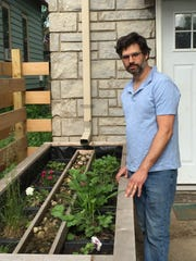 Aaron Pierce diverted his home's roof downspout into a StormGUARDEN designed by Stormwater Solutions Engineering LLC of Milwaukee. Use of this green infrastructure, a 10-foot-long box planted with flowers and grasses, allowed Pierce to disconnect the downspout from the city's combined sanitary and storm sewer.