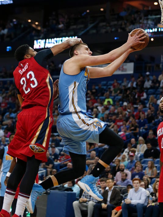 Denver Nuggets forward Nikola Jokic goes to the basket against New Orleans Pelicans forward Anthony Davis (23) in the first half of an NBA basketball game in New Orleans, Tuesday, April 4, 2017. (AP Photo/Gerald Herbert)