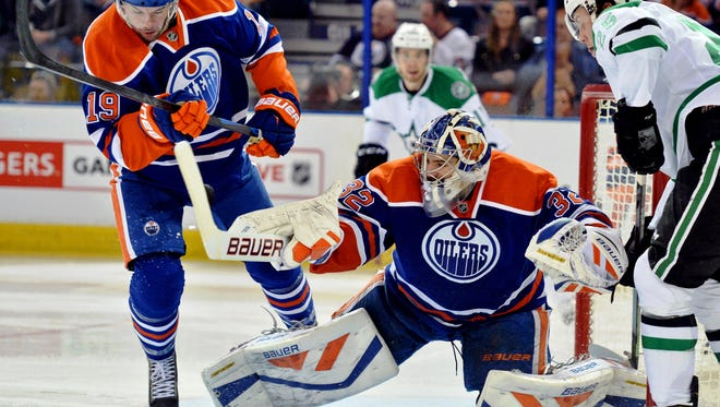 Edmonton Oilers goalie Richard Bachman (32) makes a save as Edmonton Oilers defenceman Justin Schultz (19) knocks over the goalie against the Dallas Stars in the second period at Rexall Place.