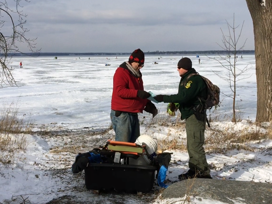 State game warden Sgt. Carl Wedin checks the fishing license of an angler before the two walk out onto the ice of Lake Champlain on Thursday, Jan. 14, 2016. Wedin says the thin ice on many bays poses a danger to inexperienced anglers, and he's keeping well away from the thinner edges as he patrols the area.