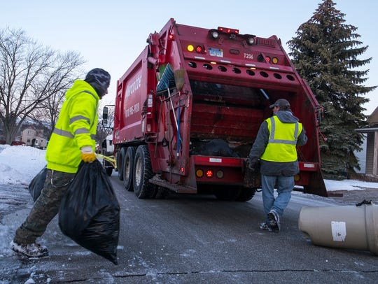 Marcotte Disposal employees Mickey Kenney, left, and Stephen Clark load garbage into the back of a garbage truck in a southside Port Huron neighborhood more than a year ago. Emterra is now the city's contracted company for refuse collection.
