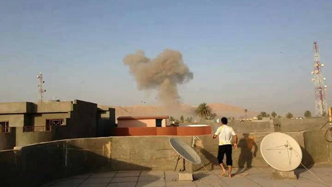 Smoke rises after a bomb attack in Tuz Khormato, 130 miles north of Baghdad.