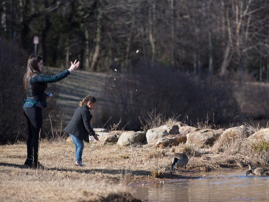 Rachel Gwinn and her daughter, Imani, 6, feed ducks