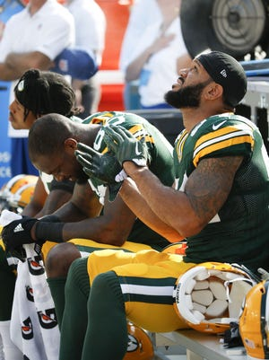Green Bay Packers players (from left) Kevin King, Martellus Bennett and Lance Kendricks sit in protest during the national anthem before their game against the Cincinnati Bengals at Lambeau Field on Sunday in Green Bay.
