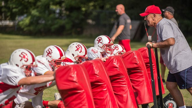 In this 2015 photo, longtime St. Philip football assistant coach Jack Brown rides the sleds during practice at Walsh Field.