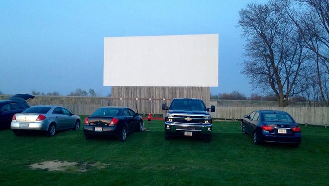 The front of the 61 Drive-In theater, located on U.S. Highway 61 just south of Maquoketa, has a grassy parking lot.