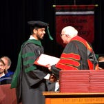 Carey President Tommy King presents Syed Ahmed with his degree. Ahmed was among the more than 80 students to graduate Saturday from William Carey's College of Osteopathic Medicine.