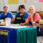 Spamcakes are presented to the crowd before being sampled by judges (from left) Jan Moldenhaur, April Hansen and Teresa Loftis. TRIBUNE PHOTO/EVAN FROST