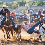Ian Austiguy of Dillon leaves his horse to tackle a steer during the PRCA rodeo at the state fair Wednesday.